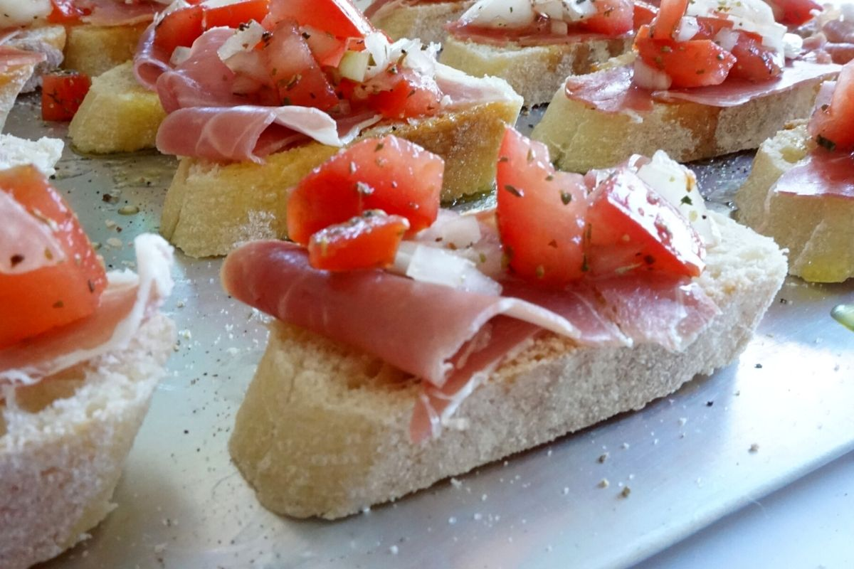 making bruschetta with prosciutto and tomatoes French baguette slices
