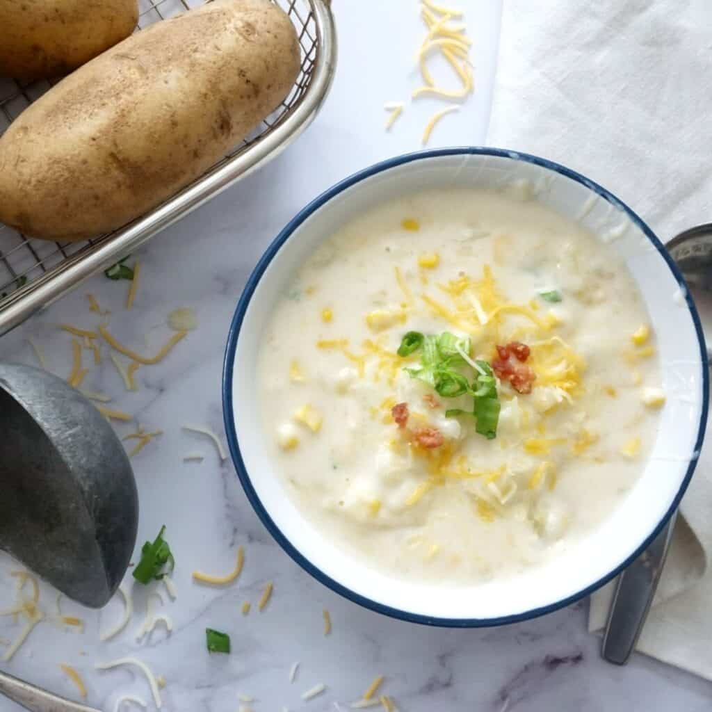 baked potato soup in a bowl with green onions cheese and bacon bits