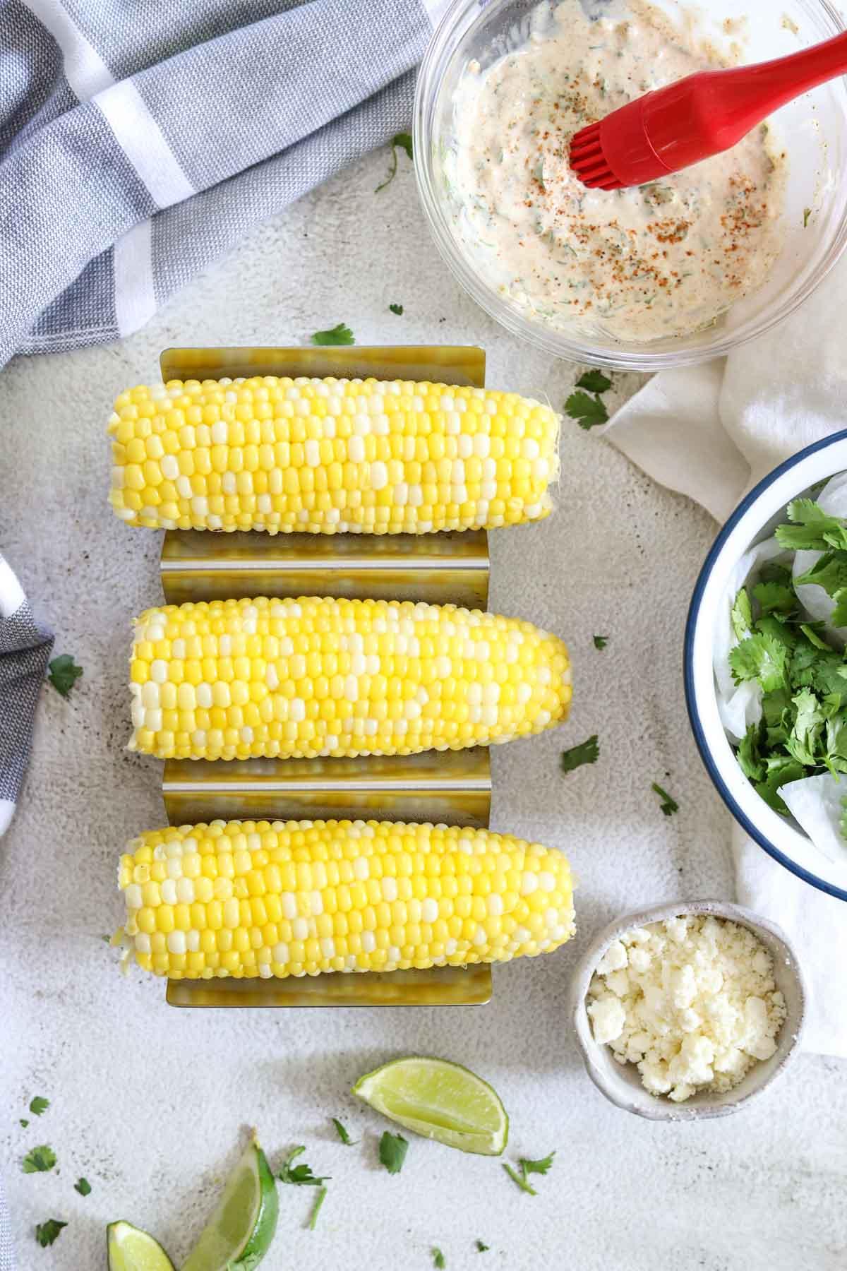three ears of yellow sweet corn on a table