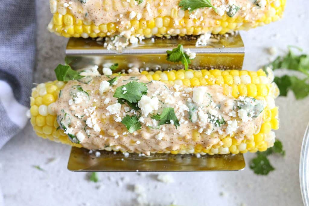cojita cheese and sauce over elote, Mexican corn