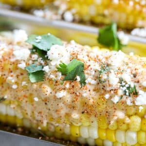 Mexican street corn with sauce, cojita cheese, cilantro