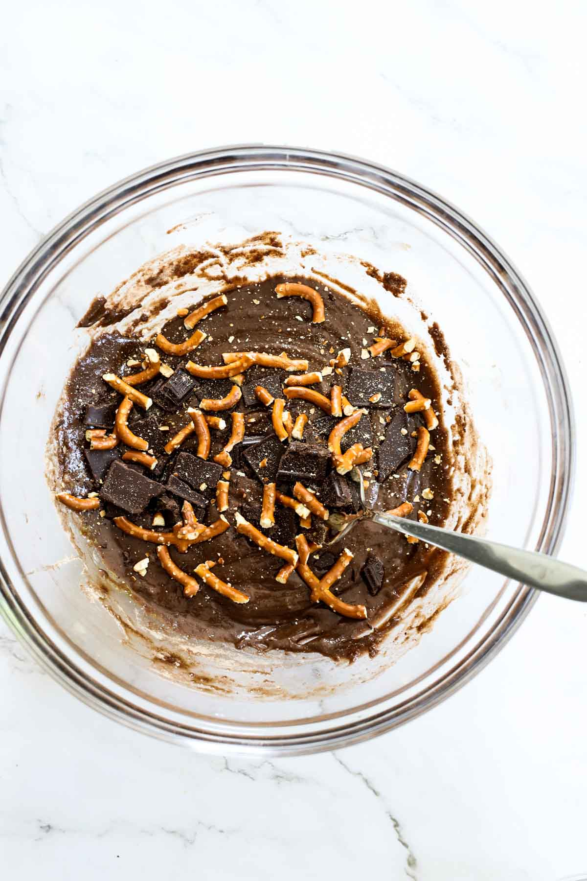 brownie batter with pretzel bits in a mixing bowl