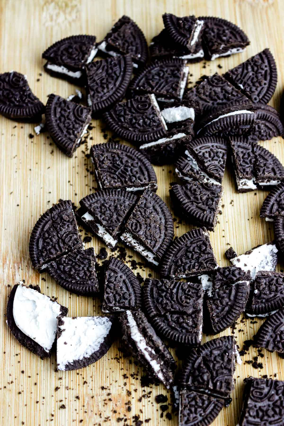 a bunch of crumbled Oreo cookies with creamy filling crushed on a table