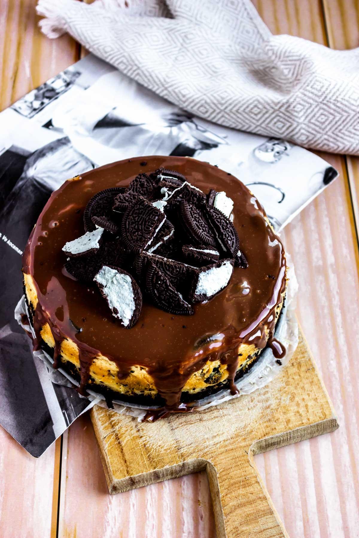 freshly made oreo cheesecake covered in chocolate ganache and crumbled cookies
