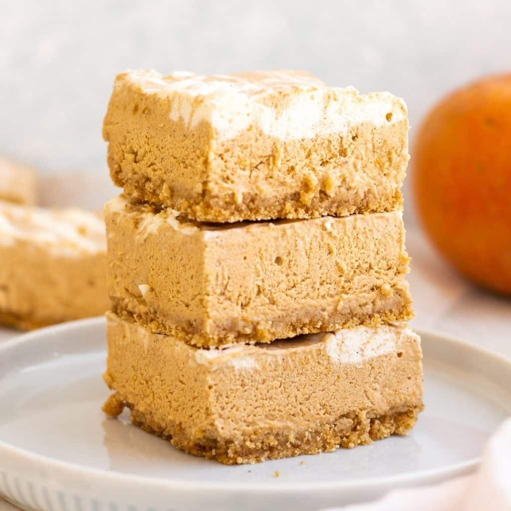 no bake pumpkin cheesecake bars stacked in a set of three