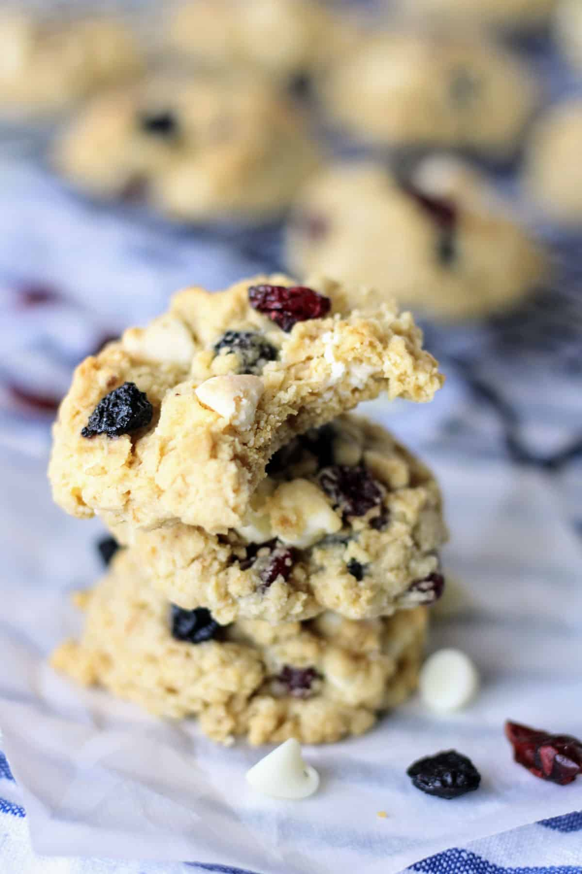stacked cookies with a bite take out with scattered craisins and dried blueberries all around