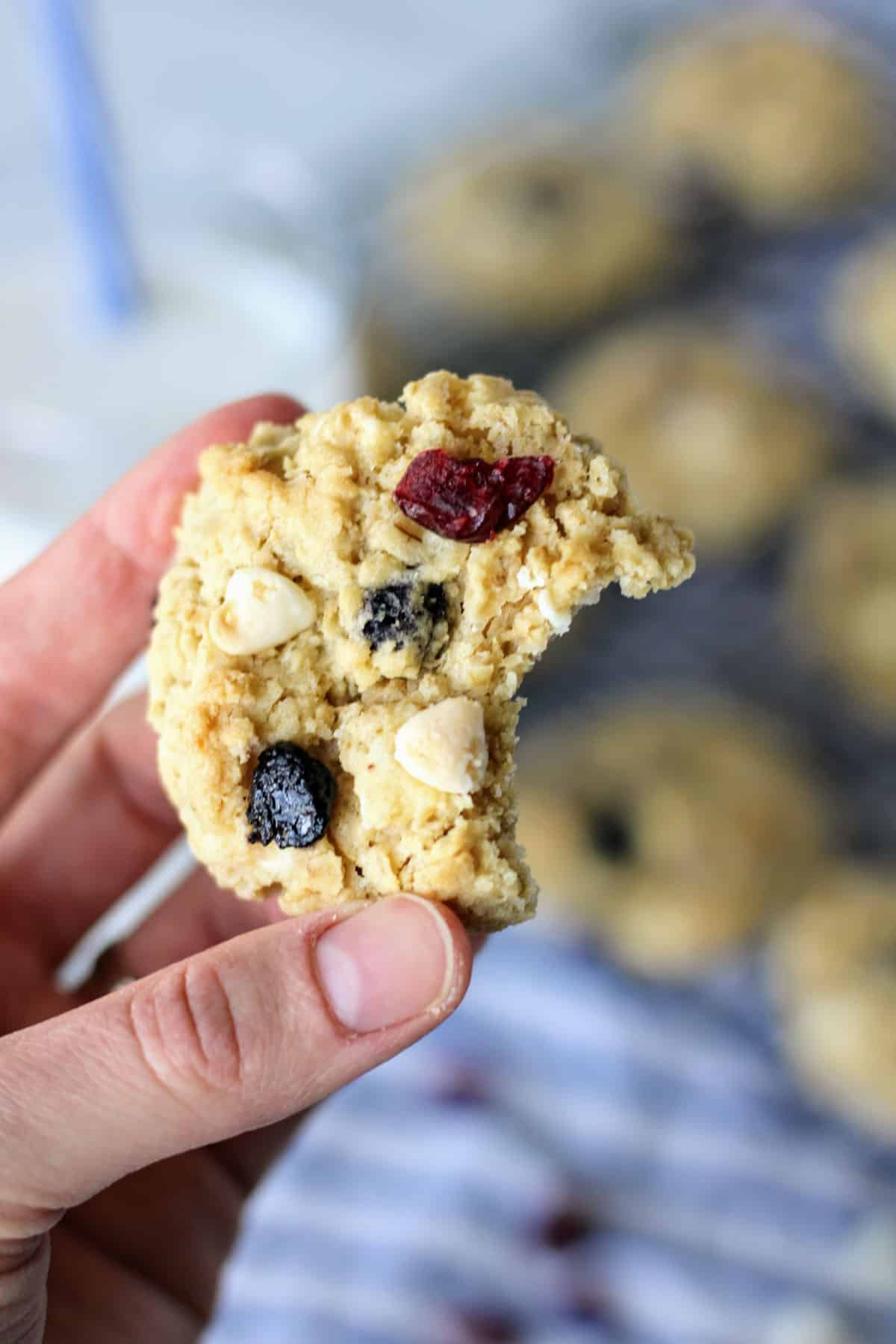 hand holding a red, white and blueberry cookie with a big bite taken out