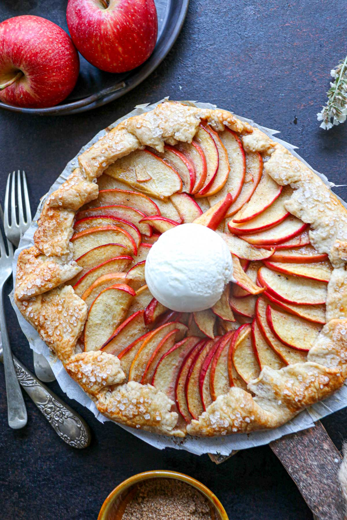 apple galette with a black background and ice cream on top with whole red apples also on the table