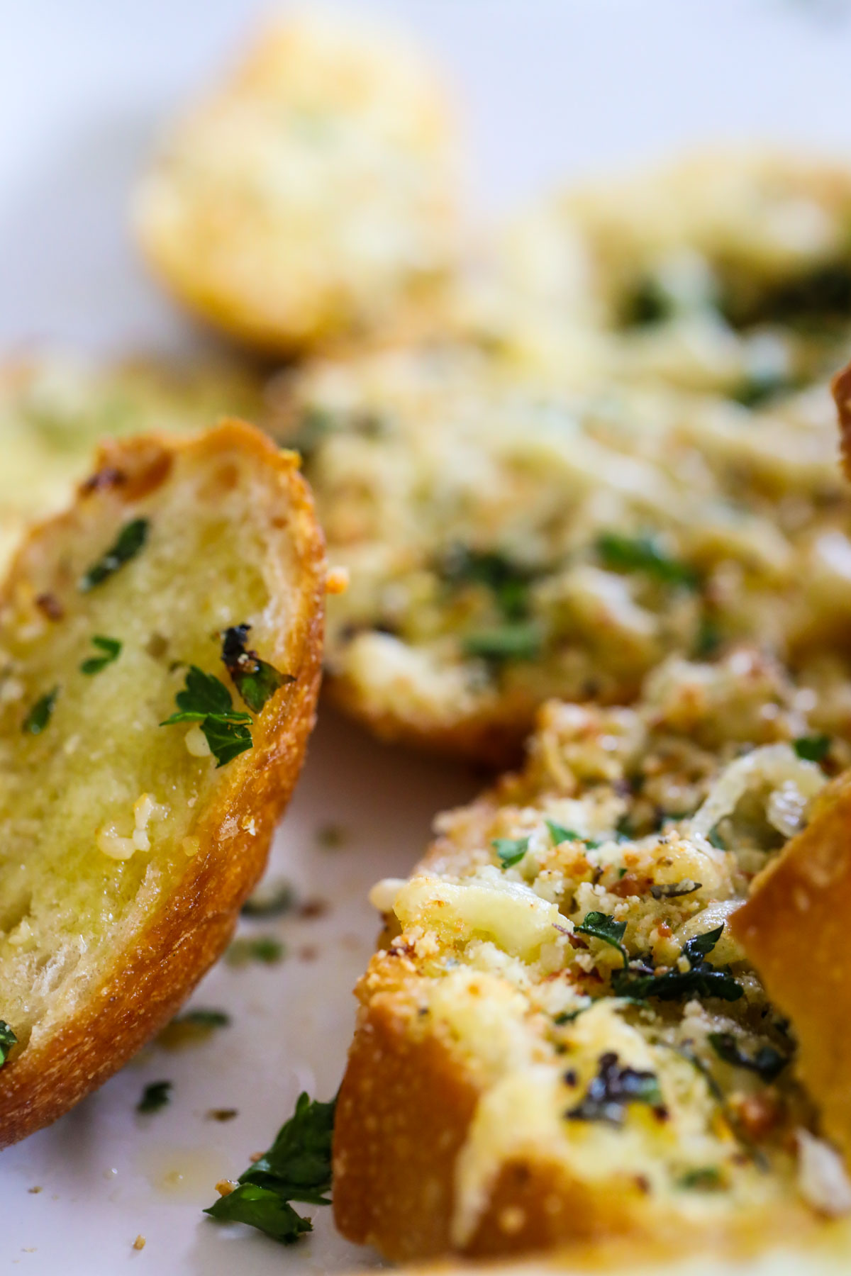 piece of garlic bread with seasonings and parsley