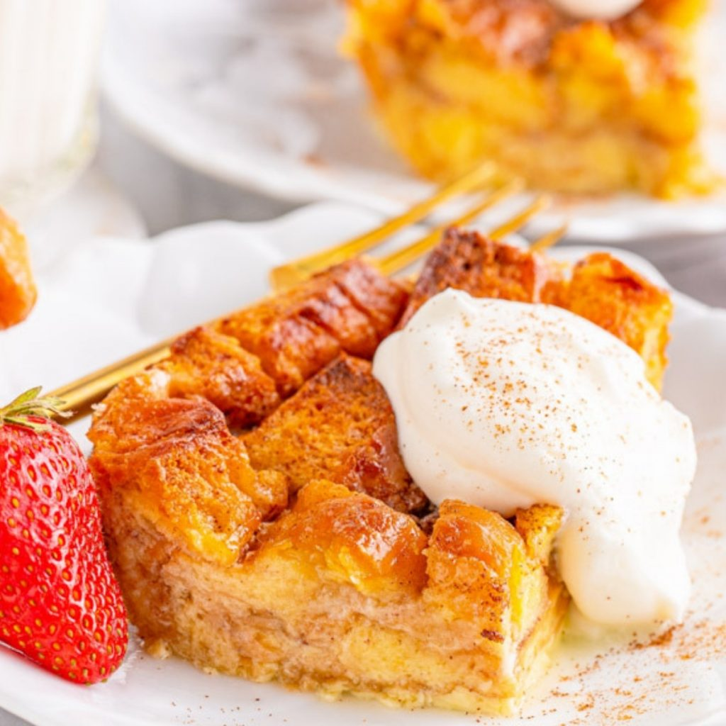 slice of honey bun bread pudding with whipped topping and strawberry on the side