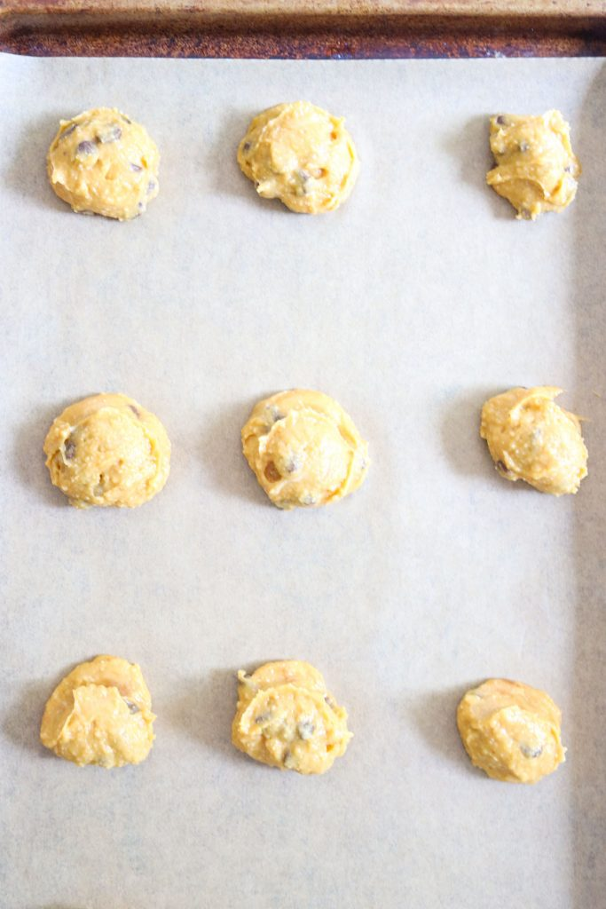 Balls of cookie dough on a baking sheet with parchment paper