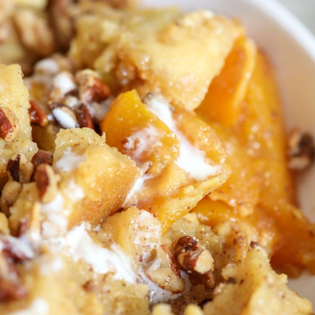 close up of peaches and cream drizzle in bread pudding