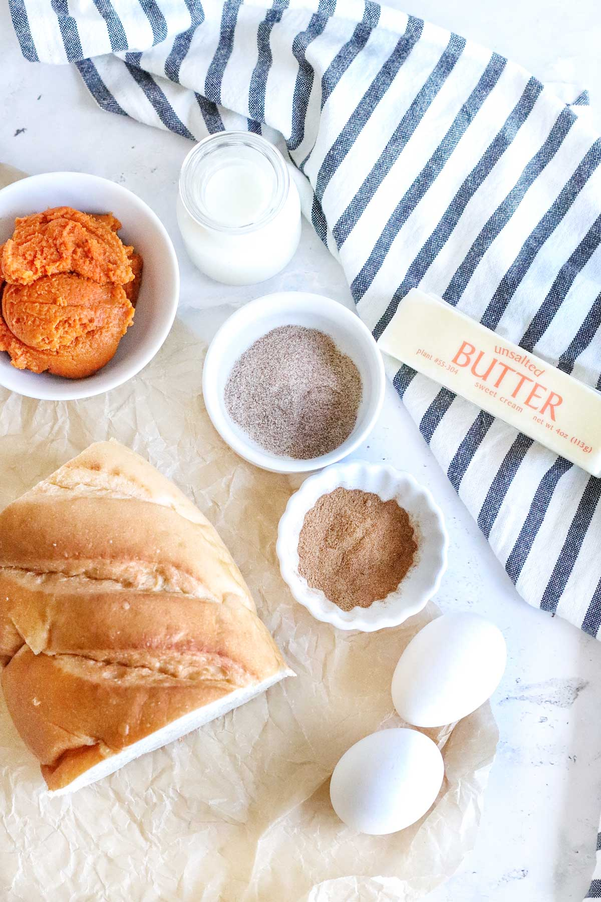 ingredients for pumpkin french toast sticks, including bread, spices, eggs, pumpkin purée and butter
