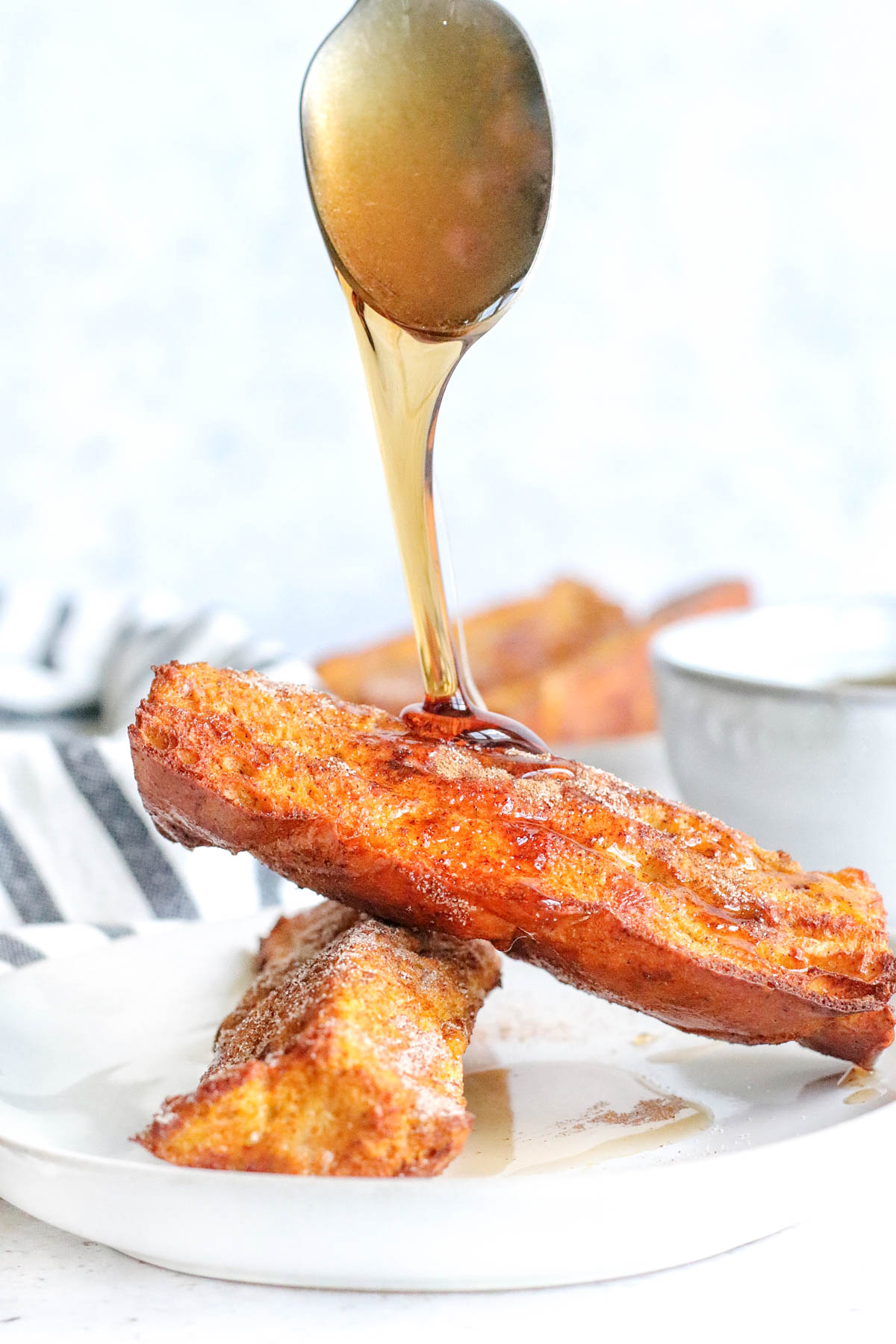 a spoon adding syrup to french toast sticks stacked on a plate