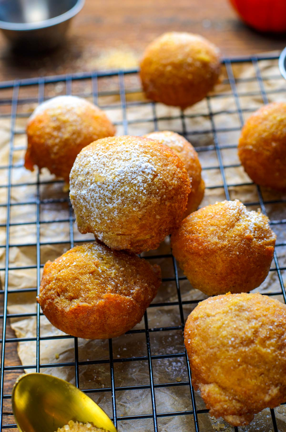 pumpkin fritters with a golden spoon and powdered sugar