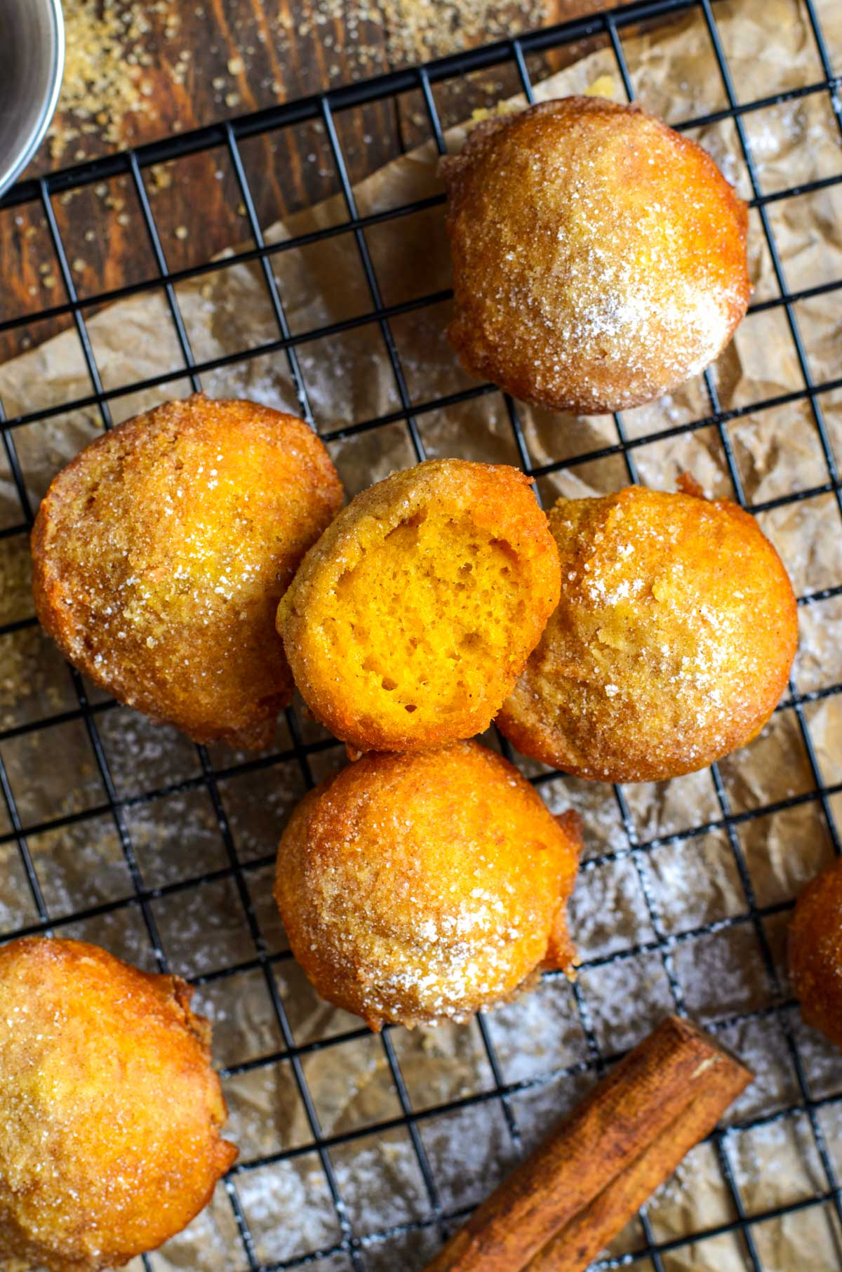 pumpkin fritters on a drying rack with a cinnamon stick