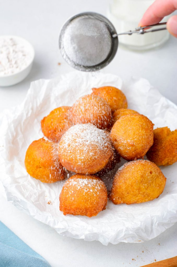 adding powdered sugar to fritters