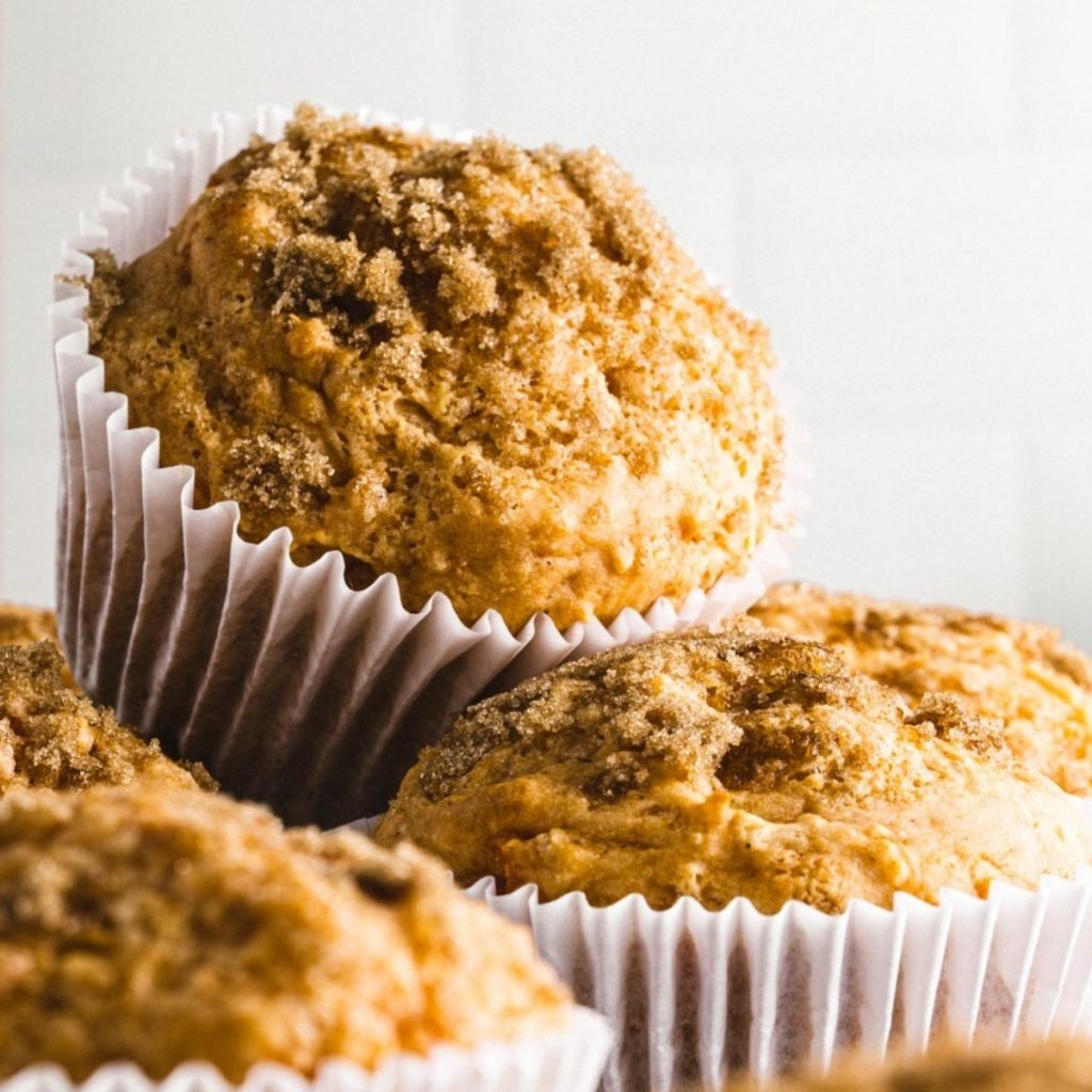 sweet potato muffins with cinnamon sugar stacked on top of one another