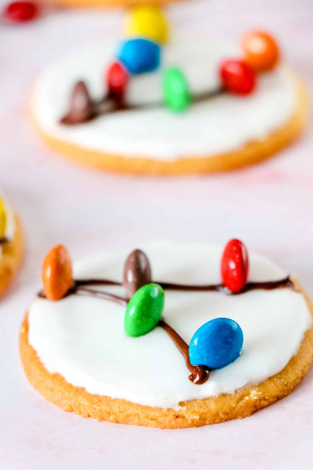sugar cookie with frosting and m&ms made to look like christmas light decorations