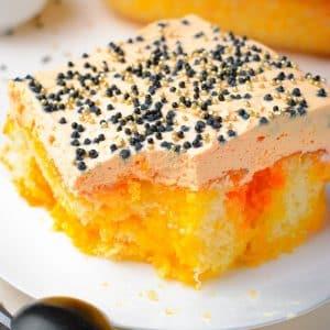 orange poke cake with black sprinkles
