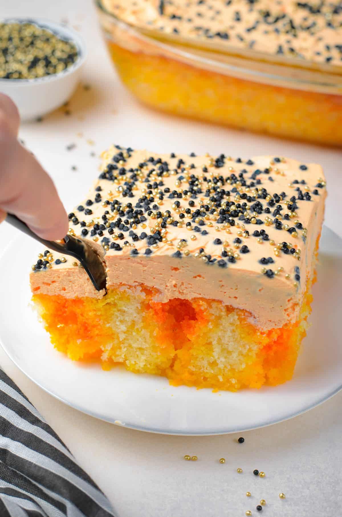 cutting into a piece of orange striped cake