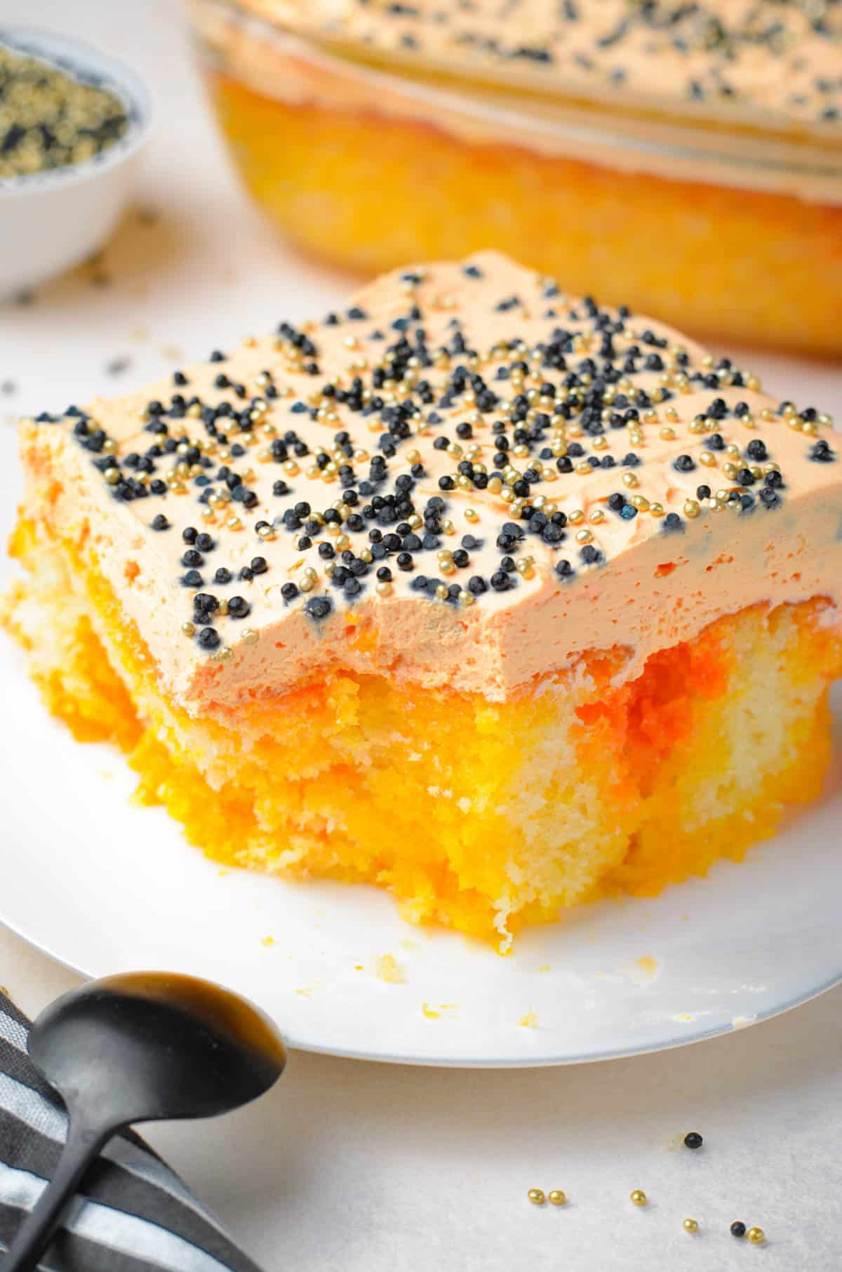 orange striped poke cake with a fork and spoon and black sprinkles