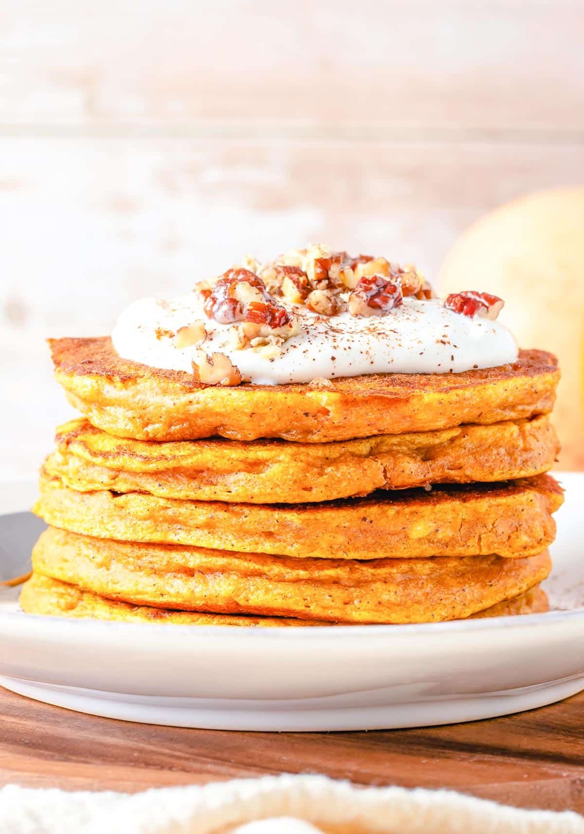 stack of 6 pumpkin pancakes with frosting and nuts