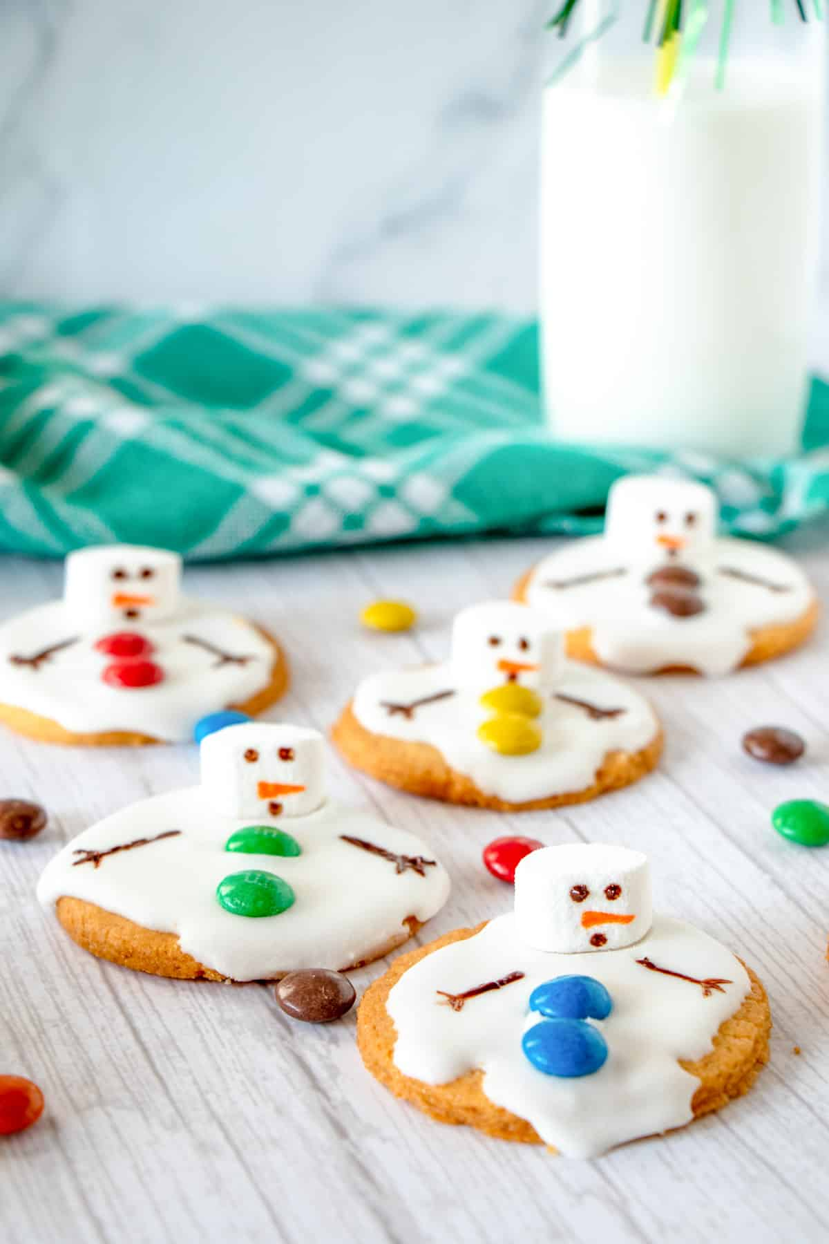 snowman cookies with a tall glass of milk