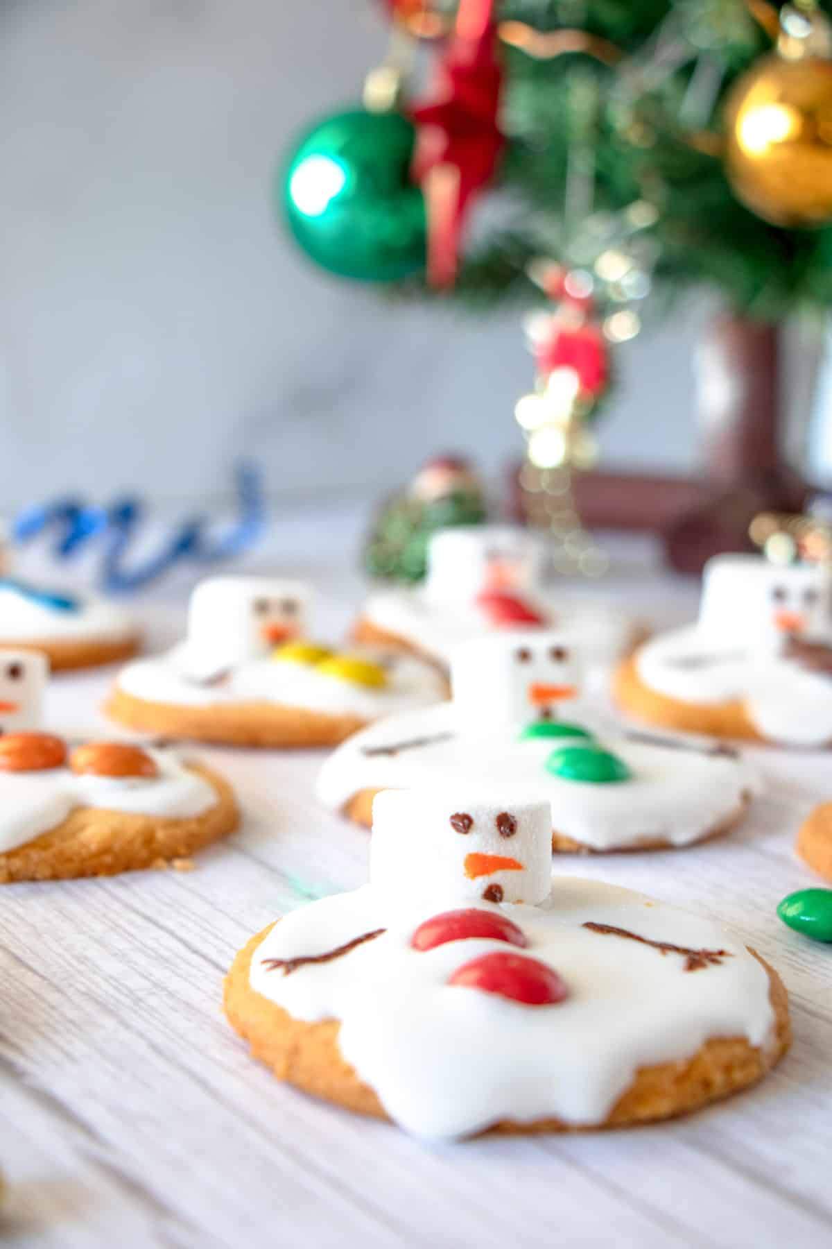 Christmas melted snowman cookies next to a tree with ornaments and Christmas decor