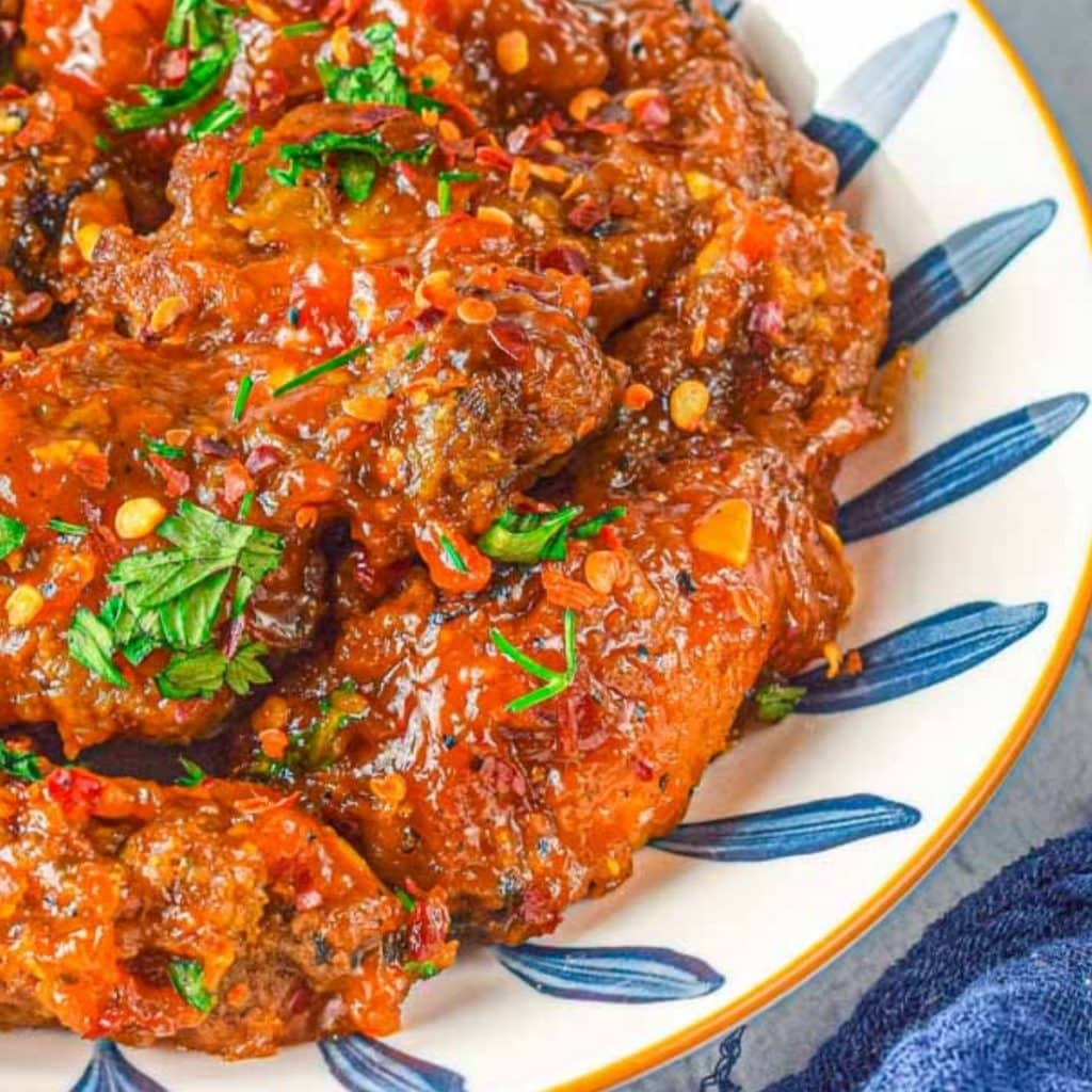 sweet thai sticky wings in a bowl with garnish