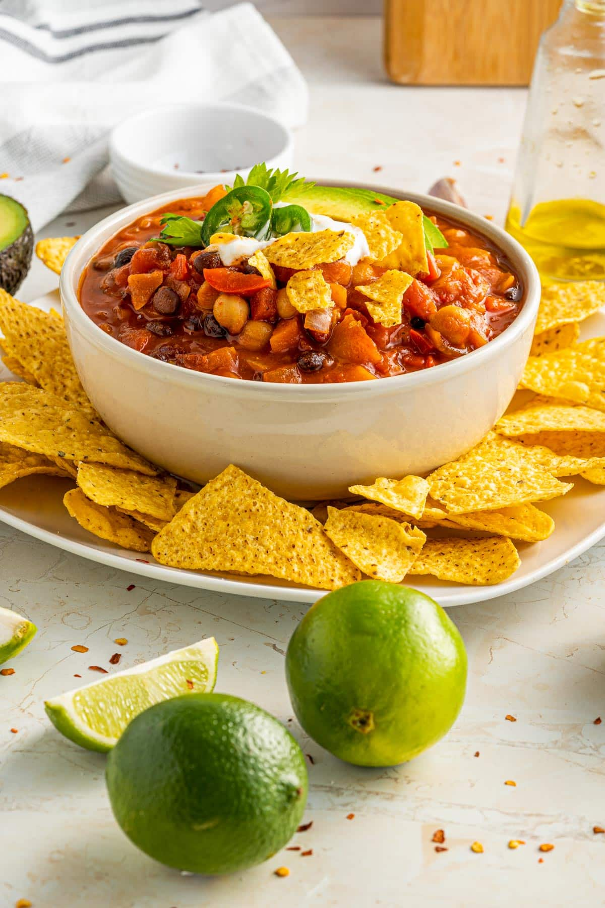 bowl of chili with limes slices and golden tortilla chips
