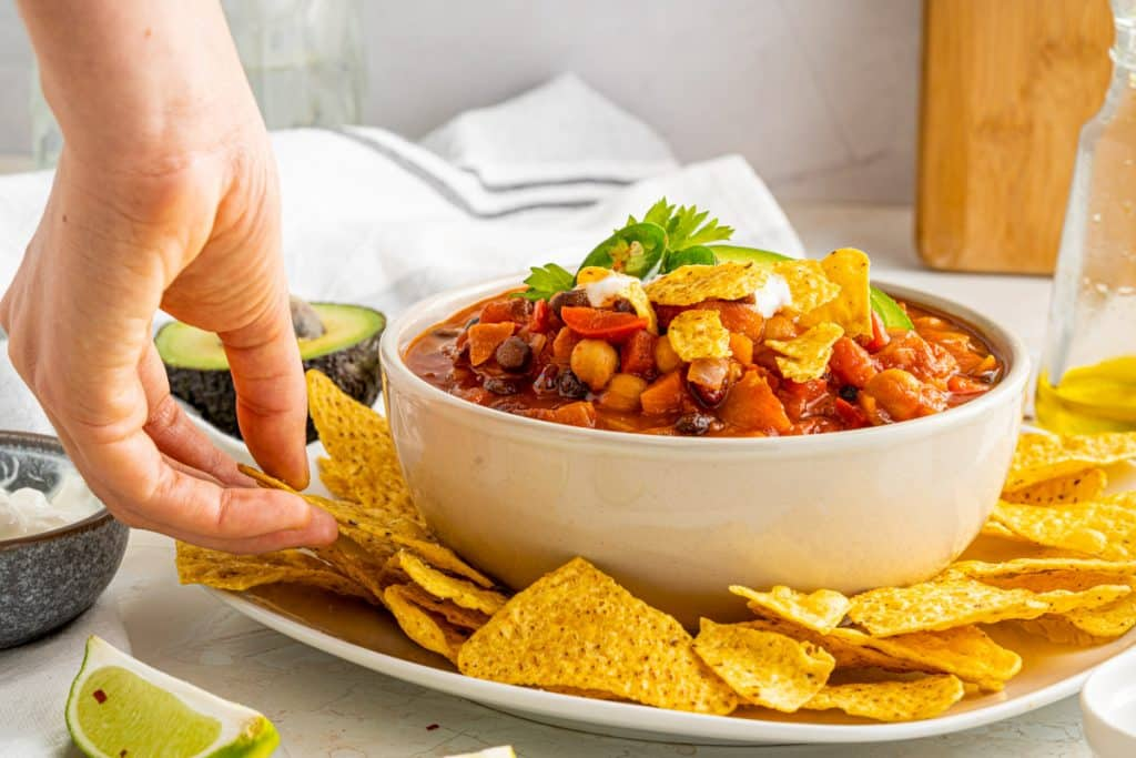 grabbing a chip for dipping in chili beans