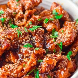 sesame chicken in a bowl with sesame seed topping and garnish